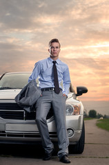 Handsome young man leaning on his car