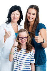 Teen girl and younger sister with dentist.