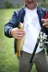 Man, holding freshly caught fish