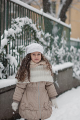 Winter portrait of a beautiful girl with knitted hat in the snow