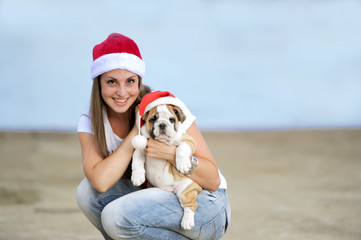 the woman in a red cap holds a puppy of breed a bulldog in hand