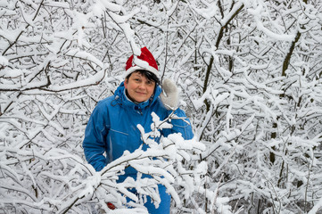 Woman in ski suit and cap of Santa Klaus  in snow-covered wood