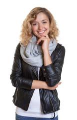 Clevere Frau mit blonden Locken und Lederjacke