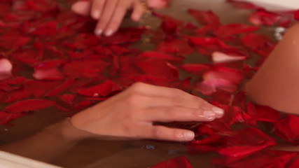 Woman relaxing in bath with rose petal.