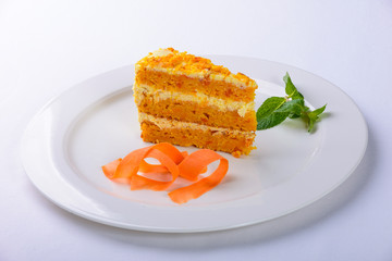 cake with carrots plate on white background
