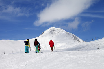 Three snowboarder on slope at sun nice day