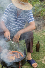 senior man with a straw hat at a barbecue grill