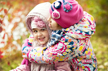 two girls playing in the park in autumn
