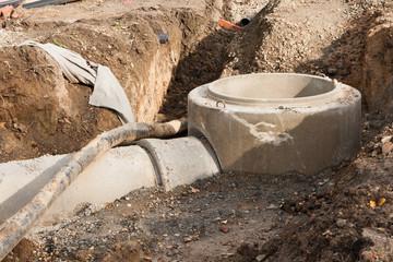 Kanalbau - Betonrohre an einem Fertigteil von einem Kanalschacht