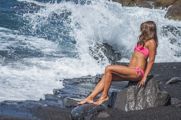 woman with on rocks near big waves and mountains