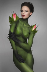 Woman in green body-art with rose burgeons
