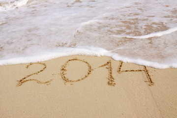 Year 2014 hand written on the  sand.