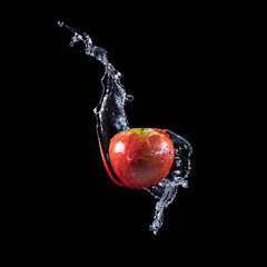 Red apple splashing into water