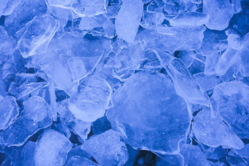 Shattered thin layers of blue ice sheets, background.