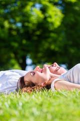 Mann und Frau liegen in Sonne auf Park Wiese