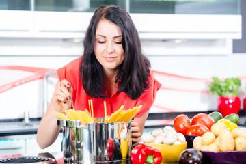 Frau kocht Pasta zuhause in Küche