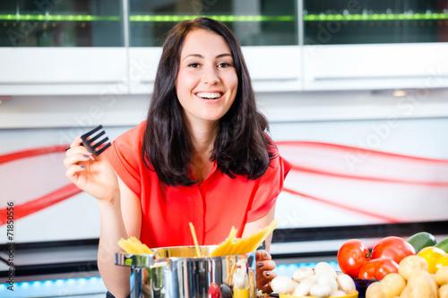 canvas print picture Frau kocht Pasta zuhause in Küche