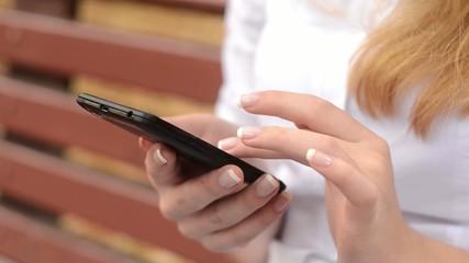 Девушка ищет что-то в своем смартфоне