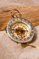 compass on beach sand