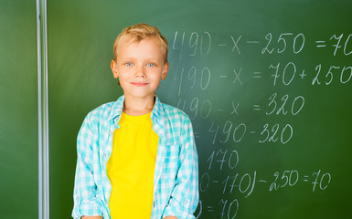 Boy in bright T-shirt stands near blackboard