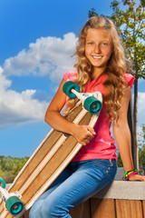 Positive girl holds skateboard sitting in park