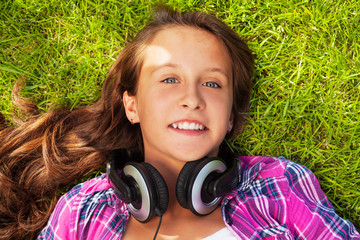 Smiling girl with headphones laying on green grass