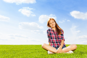 Beautiful girl sits on bright grass and smiles