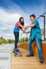 Girl learns riding skateboard holding boy's hands