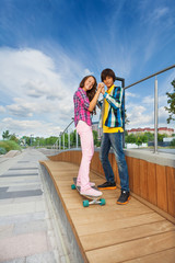 Boy holding hands of girl on skateboard