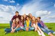 Happy international kids sit close on grass