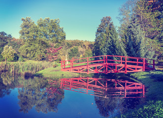 Vintage retro filtered picture of red bridge in garden.