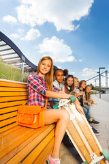 View of beautiful girls sitting on wooden bench