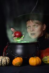 Hexe hält roten Apfel über Kessel mit viel grünem Dampf