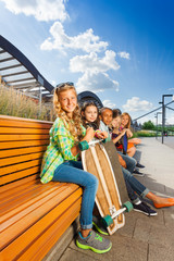 Nice girls sitting on wooden bench in urban style