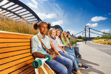 Beautiful girls sitting on wooden bench in a row