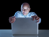 businessman at night on computer watching porn online gambling poster
