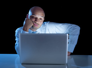 overworked businessman working on computer late night exhausted