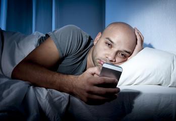 mobile phone addict man awake in bed using internet