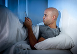 nternet addict man awake in bed using digital pad or tablet poster
