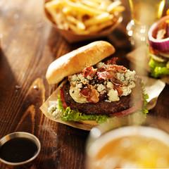 gourmet bleu cheese burgers with beer being poured