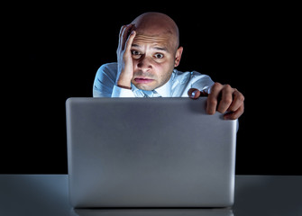 stressed businessman working on computer laptop late at night