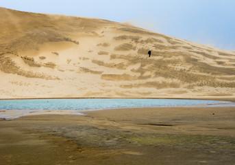 Man climbing up a sand dune