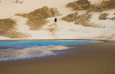 Hiker climbing up a sand dune