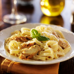 fettuccine alfredo pasta with grilled chicken at night