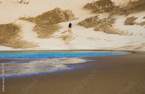 canvas print picture Hiker climbing up a sand dune