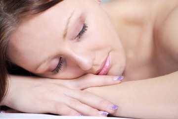 Pretty lady sleeping with head resting on hands