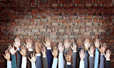 Group of Diverse Business Hands Raised on Brick Wall