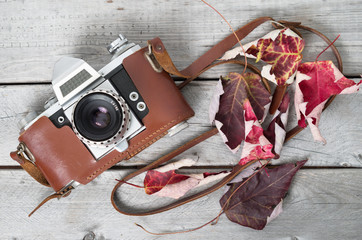Very old SLR on wooden background with autumn leaves