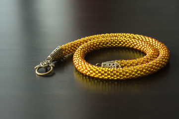 Yellow necklace from beads on a dark wooden surface