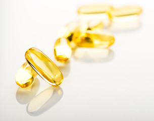 shiny yellow vitamin e fish oil capsule on white background